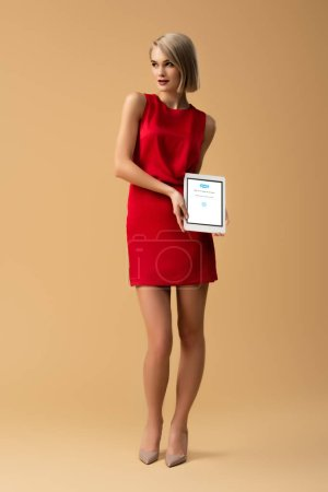 Photo for Full length view of woman in red dress holding digital tablet with skype app on screen - Royalty Free Image