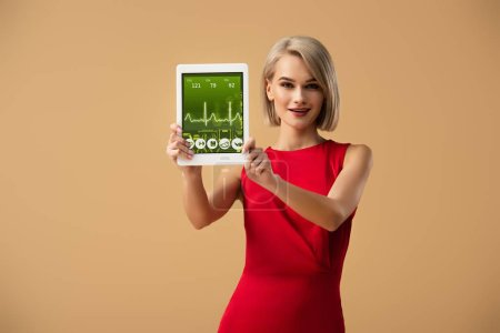 Photo for Beautiful woman in red dress holding digital tablet with health app on screen isolated on beige - Royalty Free Image