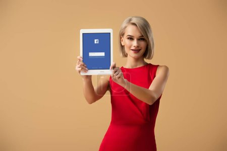 Photo for Beautiful woman in red dress holding digital tablet with facebook app on screen isolated on beige - Royalty Free Image