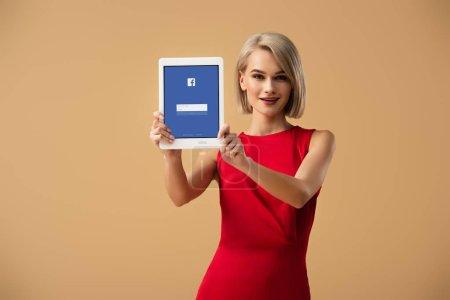 Photo pour Belle femme en robe rouge tenant tablette numérique avec application facebook à l'écran isolé sur beige - image libre de droit