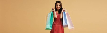 Photo for Panoramic shot of beautiful young woman in red dress holding shopping bags isolated on beige - Royalty Free Image