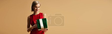 Photo for Panoramic shot of beautiful young woman in red dress holding gift box isolated on beige - Royalty Free Image