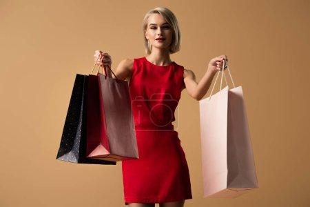 Foto de Hermosa mujer joven en vestido rojo sosteniendo bolsas aisladas en beige - Imagen libre de derechos