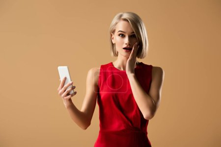 Photo for Surprised young woman in red dress holding smartphone isolated on beige - Royalty Free Image