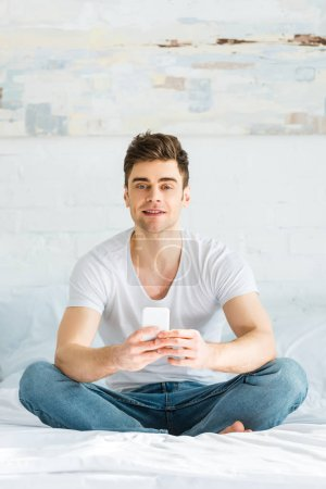 Photo for Handsome man in t-shirt and jeans sitting on bed and holding smartphone in bedroom - Royalty Free Image