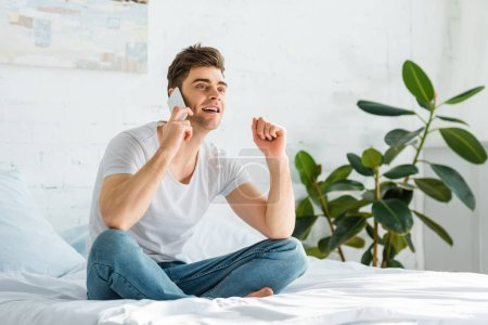 handsome man in t-shirt and jeans sitting on bed and talking on smartphone in bedroom
