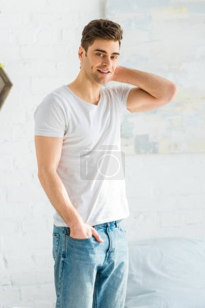 Photo for Handsome man in white t-shirt and jeans standing near bed in bedroom - Royalty Free Image