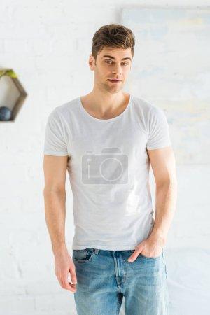 Photo pour Bel homme en t-shirt blanc et jeans debout sur fond blanc - image libre de droit