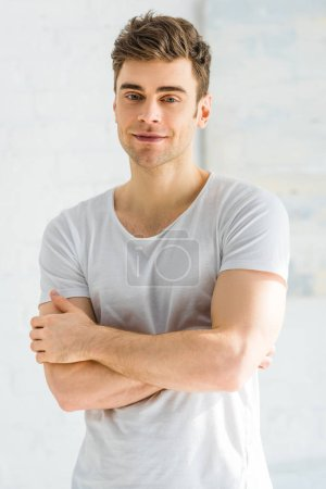 handsome man in white t-shirt standing and smiling with crossed arms on white background