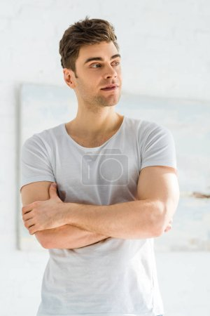 handsome man in white t-shirt standing with crossed arms in bedroom
