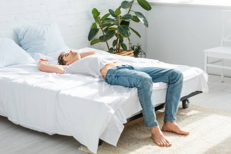 Photo for Handsome man in t-shirt and jeans lying on back on bed in bedroom - Royalty Free Image