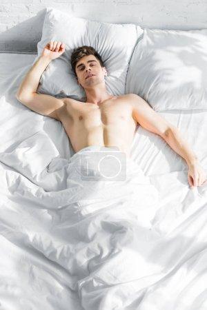 Photo pour Bel homme couché sur le lit avec torse nu à la maison - image libre de droit