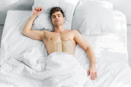handsome man lying on bed under blanket with bare torso at home