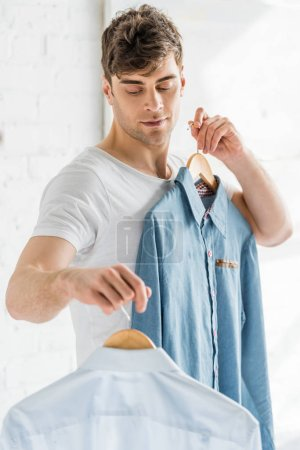 Photo for Handsome man in white t-shirt holding shirts on white textured background - Royalty Free Image