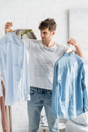 Photo for Handsome man in white t-shirt holding shirts in bedroom - Royalty Free Image