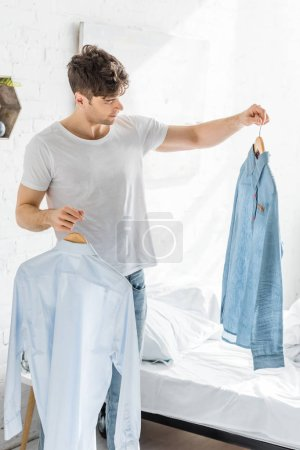 Photo for Handsome man in white t-shirt standing near bed and holding shirts in bedroom - Royalty Free Image