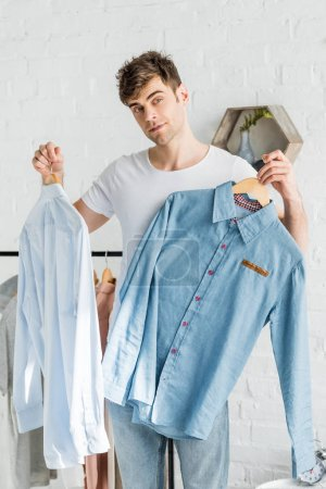 Photo for Handsome man in white t-shirt standing and holding shirts in bedroom - Royalty Free Image