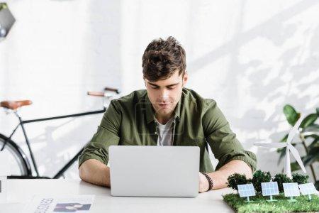 Photo pour Beau architecte en chemise verte assis à table avec ordinateur portable et le moulin à vent, modèles de panneaux solaires au bureau - image libre de droit
