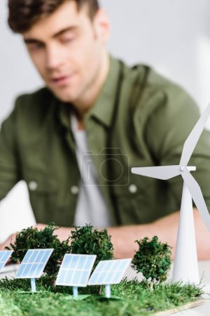Photo for Selective focus of architect at table with windmill, trees, solar panels models in office - Royalty Free Image