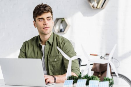 Photo for Selective focus of handsome architect at table with laptop, solar panels models, windmills and trees models in office - Royalty Free Image