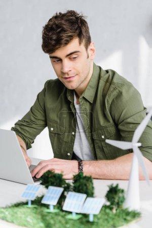 Foto de Enfoque selectivo del guapo arquitecto escribiendo en la computadora portátil cerca de molino de viento, árboles y paneles solares modelos en oficina - Imagen libre de derechos