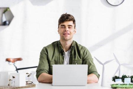 Foto de Apuesto arquitecto sentado en la mesa, escribiendo en la laptop y sonriendo junto a modelos de molinos y edificios de oficina - Imagen libre de derechos