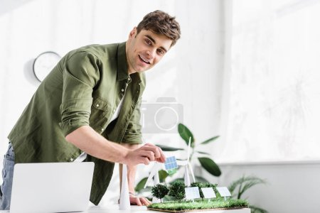 Photo for Handsome architect standing and putting solar panel model on grass near trees, windmills model and laptop on table in office - Royalty Free Image