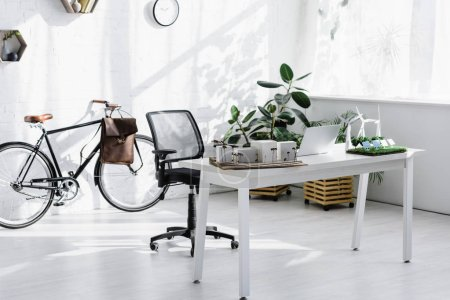 bicycle near brick wall, chair, table with laptop and buildings, trees, windmills models in office