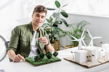 Foto de Handsome architect smiling and holding solar panels models over grass on table in office - Imagen libre de derechos