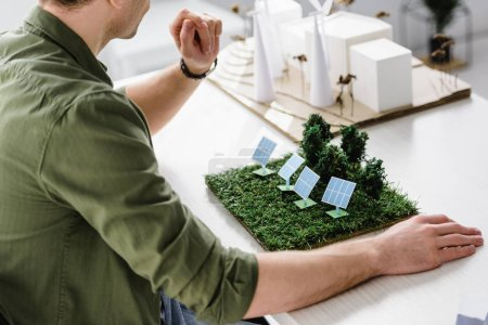 Photo for Cropped view of architect sitting at table with solar panels and trees models in office - Royalty Free Image