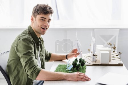 Photo for Architect in green shirt sitting at table and holding windmill model in office - Royalty Free Image