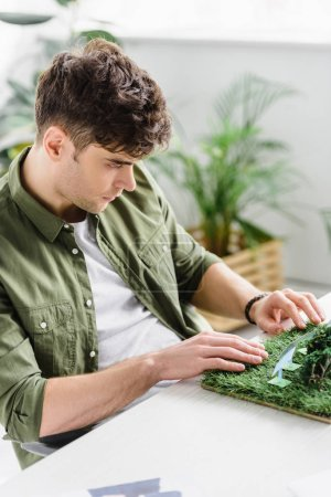 Photo pour Selective focus of handsome architect sitting at table with solar panels models on grass in office - image libre de droit
