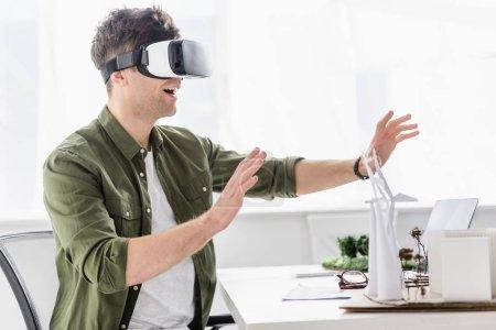 Foto de Arquitecto en casco de realidad virtual sentado en mesa con modelos de molinos de viento, edificios y árboles en oficina - Imagen libre de derechos