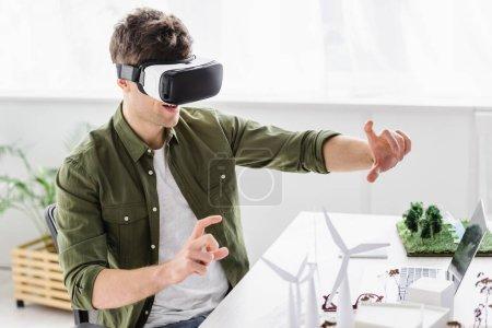 Foto de Arquitecto en casco de realidad virtual sentado en mesa con modelos de ordenador portátil, molinos de viento y árboles en oficina - Imagen libre de derechos
