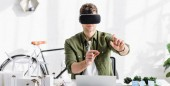 architect in virtual reality headset at table with laptop and trees, solar panels models in office