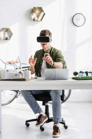 Photo for Architect in black virtual reality headset at table with laptop and windmills, buildings, trees, solar panels models in office - Royalty Free Image