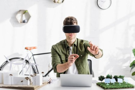 Photo for Architect in virtual reality headset at table with laptop and models in office - Royalty Free Image
