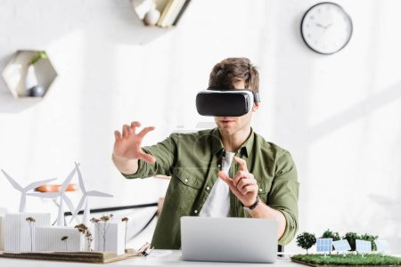 Photo for Architect in virtual reality headset sitting at table with laptop and windmills, buildings, trees, solar panels models in office - Royalty Free Image