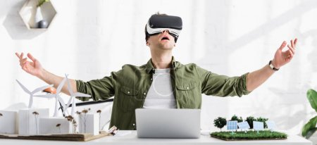 Photo for Panoramic shot of architect in reality headset at table with laptop and windmills, buildings, solar panels models in office - Royalty Free Image