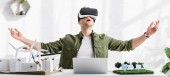 panoramic shot of architect in reality headset at table with laptop and windmills, buildings, solar panels models in office