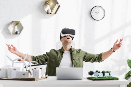 Photo for Excited architect in virtual reality headset sitting at table with laptop and models in office - Royalty Free Image
