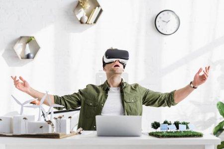Foto de Arquitecto muy contento en el casco de realidad virtual sentado en mesa con ordenador portátil y modelos en la oficina - Imagen libre de derechos