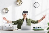 excited architect in virtual reality headset sitting at table with laptop and models in office