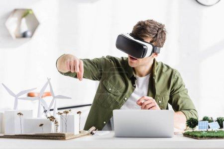 Foto de Arquitecto en casco de realidad virtual negro sentado en la mesa con ordenador portátil y molinos de viento, edificios, árboles, modelos de paneles solares en la oficina - Imagen libre de derechos