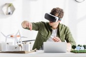 architect in black virtual reality headset sitting at table with laptop and windmills, buildings, trees, solar panels models in office