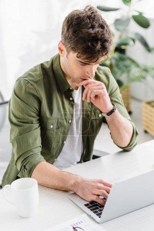 schöner Geschäftsmann in grünem Hemd sitzt mit Laptop am Tisch und tippt im Büro