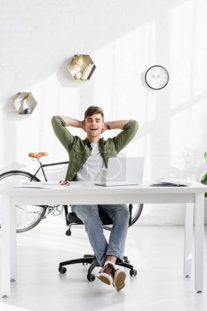 handsome businessman in green shirt sitting at table with laptop and smiling in office