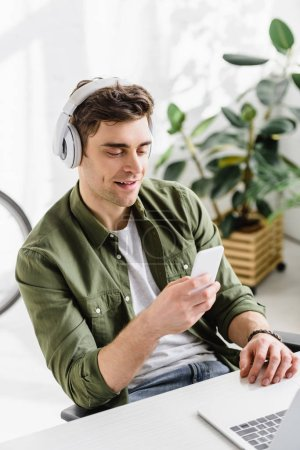 bel homme d'affaires en chemise et écouteurs assis à table avec ordinateur portable, tenant smartphone dans le bureau