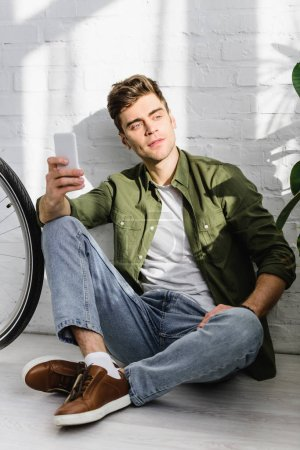 handsome man in green shirt holding smartphone, sitting near brick wall and bicycle in office