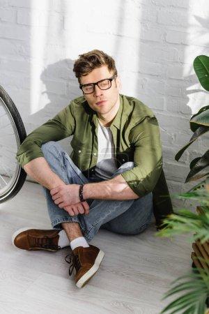 Photo pour Bel homme en chemise verte, jeans et lunettes assis sur le sol près du mur de briques, vélo et plantes dans le bureau - image libre de droit